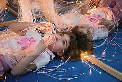 Young girl with physical and leaning disabilities playing with a string of lights,
