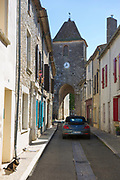 13th Century medieval gateway clock tower, VW Beetle car and dog in ancient bastide town of Duras in Aquitaine, France