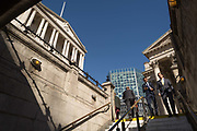 Businessmen descend the steps leading down into Bank Underground station, beneath the Bank of England and neo-classical pillars of Royal Exchange in the City of London - the capitals financial centre aka The Square Mile, on 27th September 2018, in London, England.