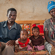 CAPTION: Damyano (far left) and Namusisi (far right) are a hearing impaired couple who have two children. They met at a SignHealth Uganda event and married soon after. Despite the fact that they have had no formal education and cannot read or write and, they live fulfilling lives thanks to the help that SignHealth provides, mostly though the dedication of volunteers in the village. LOCATION: Kankamba Village, Lwengo District, Central Region, Uganda. INDIVIDUAL(S) PHOTOGRAPHED: From left to right: Damyano Kato, Louis Wanyana, Bwogi Kato and Namusisi Kato.