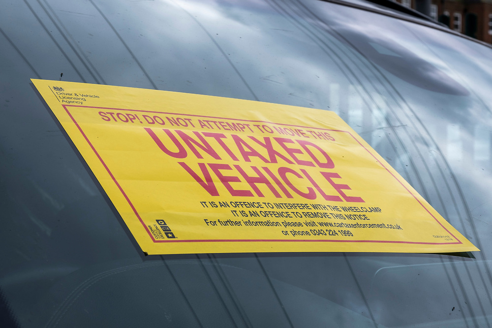 A bright yellow DVLA sign informing a driver of the wheel clamp on their vehicle in a side street on the 15th of July 2021 in Folkestone, Kent, United Kingdom. The DVLA use automatic number plate readers to locate untaxed vehicles on the streets and clamps them until tax and fines have been paid. A clamped vehicle cannot be moved until it is removed. (photo by Andrew Aitchison / In pictures via Getty Images)