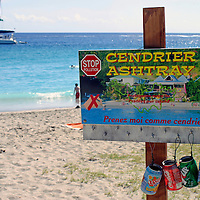 A sign offers portable ashtrays to smokers at Shell Beach on St. Barts in the Caribbean, a popular cruise destination.