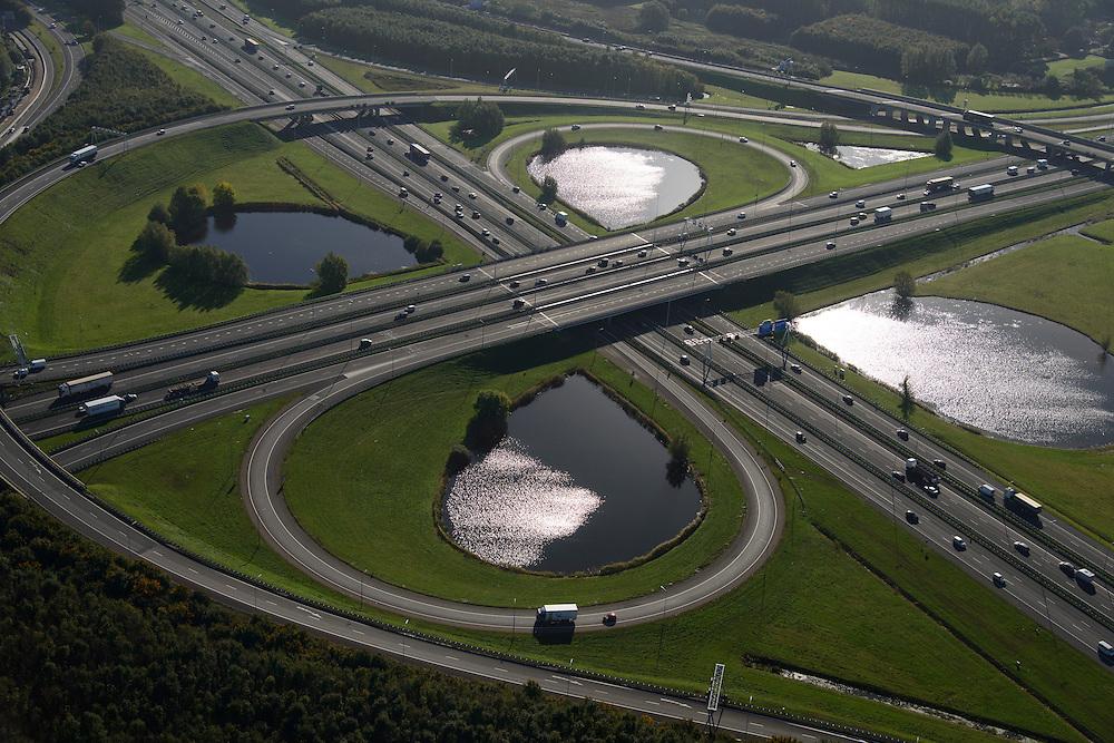 Nederland, Utrecht, Stadsdeel Leidsche Rijn, 24-10-2013; knooppunt Oudenrijn, ongelijkvloerse kruising van de snelwegen A12 (links - rechts) en A2, klaverblad met fly-overs (eigenlijk klaverturbine). Het oudste verkeersknooppunt van Nederland, de foto is gemaakt in noordoostelijke richting. De waterpartijen van het verkeersplein vormen niet alleen een landschappelijke invulling voor de restruimte, maar dienen ook als bron voor bluswater ingeval calamiteiten.<br /> Oudenrijn, junction of the A12 and A2 motorways, with cloverleaf flyovers (actually clover turbine). The oldest traffic hub in the Netherlands, the picture is taken in a northeasterly direction. The water features not only as a scenic element, but also serve as a source of fire fighting water in case of emergencies.<br /> luchtfoto (toeslag op standard tarieven);<br /> aerial photo (additional fee required);<br /> copyright foto/photo Siebe Swart