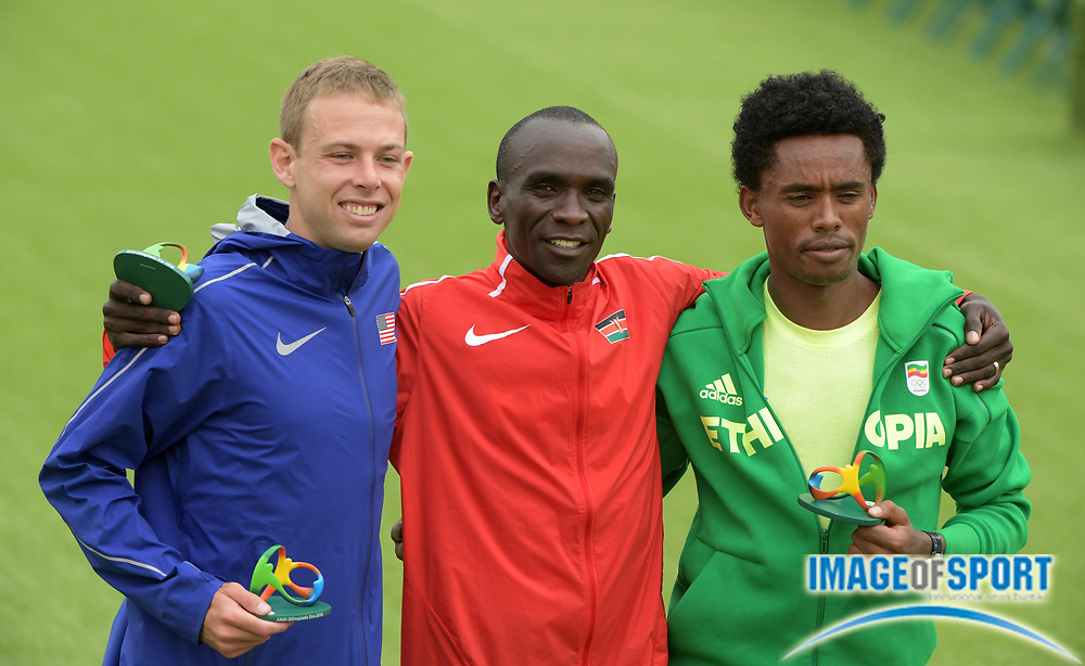 Aug 21, 2016; Rio de Janeiro, Brazil; Marathon gold medalist Eliud Kipchoge (KEN), center, poses with silver medalist Feyisa Lilesa (ETH), right, and bronze medalist Galen Rupp (USA) during the Rio 2016 Summer Olympic Games at Sambodromo.