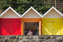 © Licensed to London News Pictures. 01/07/2015. Scarborough, UK. A lady escapes the heat in her beach hut on Scarborough beach. Britain is set to sizzle in temperatures of up to 34C (93F) today, with forecasters predicting the hottest day for several years. A tropical air mass moving from North Africa, Spain and Portugal means that we could be hotter than Rio de Janeiro. Photo credit : Andrew McCaren/LNP