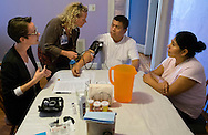 17 NOV. 2016 -- ST. LOUIS-- Hector Flores (center), a patient at Casa de Salud, a health clinic that works with members of the St. Louis immigrant community, talks with Casa de Salud GUIA Case Manager Mary Shannon (left) as volunteer nurse Vicki Moran checks his blood pressure and his wife Maria Herrera listens during a visit at Flores' home in St. Louis Thursday, Nov. 17, 2016. Flores participates in a home health program designed to educate and improve outcomes for patients with diabetes or pre-diabetes conditions. Photo © copyright 2016 Sid Hastings.