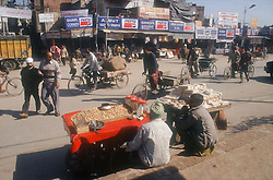 Street scene in Amritsar outside the golden temple with peanut stall; sweet stall; bicycle; rickshaws and Pepsi adverts,