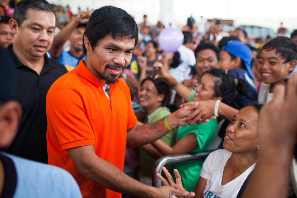 Manny Pacquiao greets a woman in the crowd inside the Tacloban City Astrodome Convention Center.<br /> <br /> Manny Pacquaio visits victims of Typhoon Yolanda in Tacloban City.  Leyte, Philippines  December 2, 2013