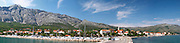 A wide panorama of the harbour jetty pier and the village and beach, the massive mountains in the background Mount Sveti Ilija mountain. Orebic town, holiday resort on the south coast of the Peljesac peninsula. Orebic town. Peljesac peninsula. Dalmatian Coast, Croatia, Europe.