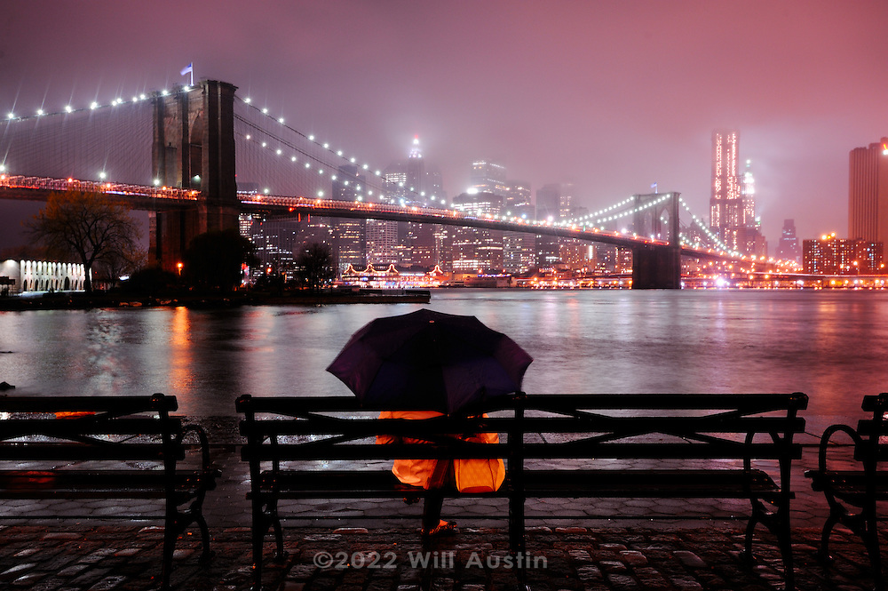 A person sits on a park bench in the rain looking at the Brooklyn Bridge.  The bridge is 1595.5 feet long and was completed in 1883.  It is a National Historic Landmark that connects Manhattan and Brooklyn by spanning the East River.