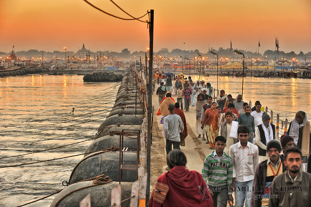 Hindu devotees walk across pontoon bridges, going back from the holy dip at Sangam, the confluence of the Ganges, Yamuna and mythical Saraswati River, during the Maha Kumbh festival