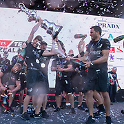 Blair Tuke sprays Peter Burling with champagne as he holds the Cup. Emirates Team New Zealand celebrate on stage after being presented with the Americas Cup on stage after beating Luna Rossa Prada Pirelli Team 7 - 3. Glen Ashby pours for Peter Burling.  Wednesday the 17th of March 2021. Copyright photo: Chris Cameron