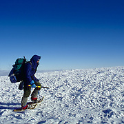 Snowshoeing above treeline on Mt. Mooselauke, New Hampshire. Hiker equipped with full winter gear including an ice axe and emergency emergency supplies