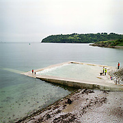 Plymouth City Council employees clean Devil's Point Pool at low tide, a man-made tidal pool on Plymouth Sound, Stonehouse, Plymouth, Devon, UK. Until the 1950s and the rise of the heated indoor swimming pool, children learnt to swim outdoors. For those close to the sea, many man-made tidal swimming pools were constructed around Britain's coastline. Heated by the sun, these tidal pools were often built to keep bathers safe from high and rough seas, which explains why so many of them are clustered in Scotland and around the surfing beaches of Cornwall. Whether they are simple swimming holes made by shoring up natural rock pools or grand lido-like pools complete with lifeguards and tea huts, they are all refreshed by good high tides.