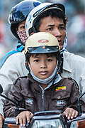 A family travels by motorbike in Vietnam.