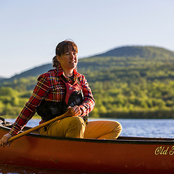 A woman paddling a canoe in the morning on Silver Lake in Piscataquis County, Maine. Near Greenville.
