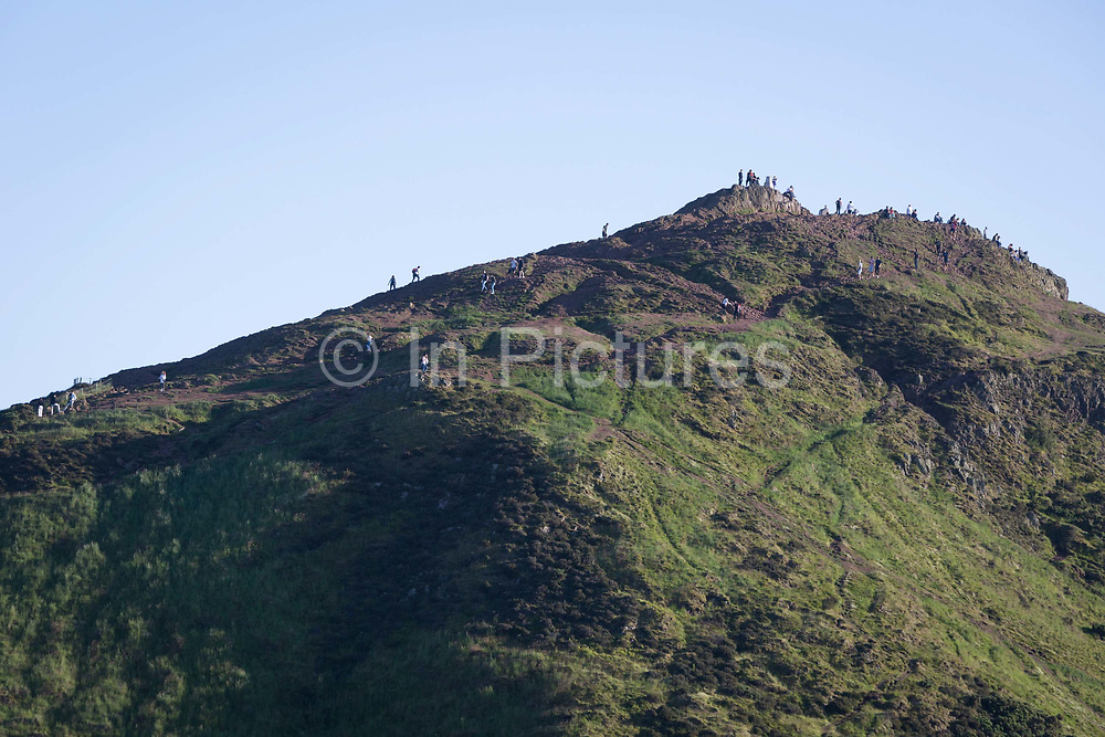 In summer evening sunshine, walkers climb the last metres to the summit of Arthurs Seat in Holyrood Park that overlooks the city of Edinburgh, on 26th June 2019, in Edinburgh, Scotland. Arthurs Seat is an extinct volcano which is considered the main peak of the group of hills in Edinburgh, Scotland, which form most of Holyrood Park, described by Robert Louis Stevenson as a hill for magnitude, a mountain in virtue of its bold design. The hill rises above the city to a height of 250.5 m 822 ft, providing excellent panoramic views of the city and beyond.