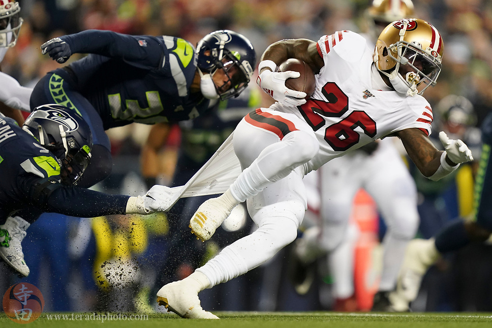 December 29, 2019; Seattle, Washington, USA; San Francisco 49ers running back Tevin Coleman (26) is tackled by Seattle Seahawks defensive end Ezekiel Ansah (94) during the first quarter at CenturyLink Field.