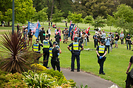 Police officers look on as protesters gather during the Sack Daniel Andrews Protest in Fawkner Park. Parts of the community are looking to hold the Victorian Premier accountable for the failings of his government that led to more than 800 deaths during the Coronavirus crisis. Victoria has recorded 36 days Covid free as pressure mounts on the Premier Daniel Andrews to relax all remaining restrictions. (Photo by Michael Currie/Speed Media)