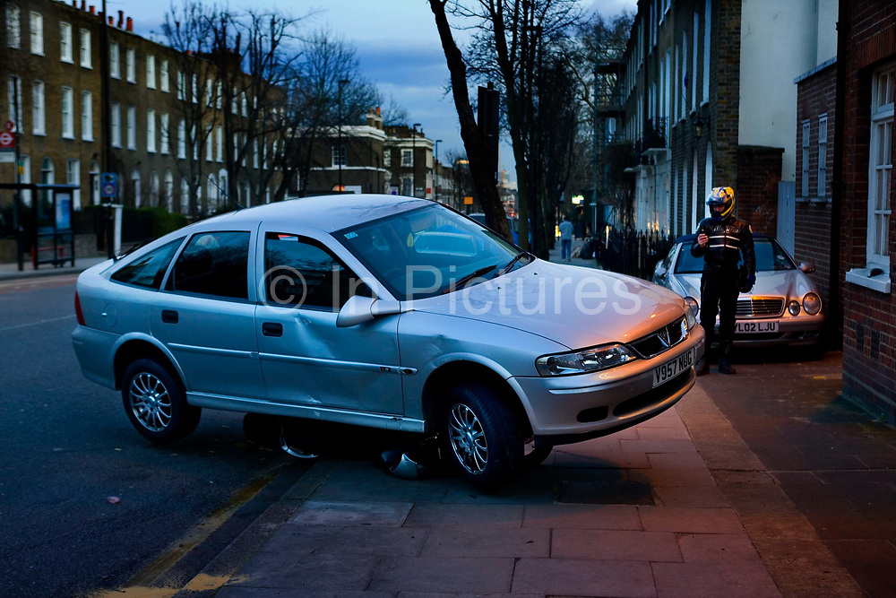 Car Wrecked on top of motorbike, Islington, London. A driver has lost control of their vehicle, mounted the kerb and come to rest on a parked motorcycle in front of a pub. Police are investigating the cause.