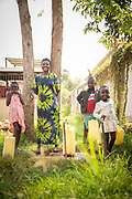 Portrait of family standing and smiling in front of clinic, Musoto, Uganda