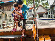 06 FEBRUARY 2015 - BANGKOK, THAILAND: A woman and her son get on the cross river ferry at the pier at Wat Kalayanamitr, a large Buddhist temple in the Thonburi section of Bangkok next to the Catholic community of Santa Cruz. The temple was built in 1825, about 50 years after Santa Cruz Church was built.          PHOTO BY JACK KURTZ