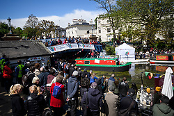 © Licensed to London News Pictures. 04/05/2019. London, UK. Members of the public line the towpath to watch a boat take part in the pageant at the Canalway Cavalcade festival in Little Venice, West London on Saturday, May 4th 2019. Inland Waterways Association's annual gathering of canal boats brings around 130 decorated boats together in Little Venice's canals on May bank holiday weekend. Photo credit: Ben Cawthra/LNP