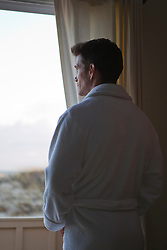 man in a white bathrobe looking out towards the beach