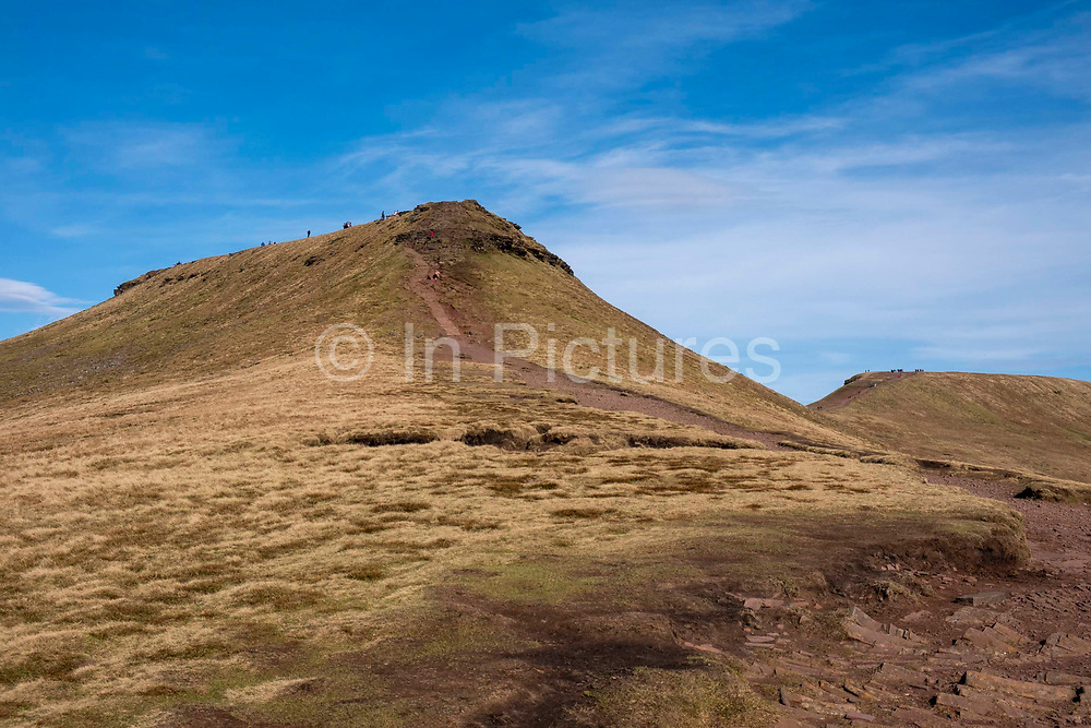Walkers explore the twinned peaks of Pen Y Fan and Corn Du in Brecon Beacons National Park, Wales, Powys, United Kingdom. The rugged path connects the two mountain peaks.  <br />  Pen Y Fan is the highest point in the Brecon Beacons hill and mountain range in South Wales. The National Park was established in 1957 due to the spectacular landscape which is rich in natural beauty and is run by the National Trust.