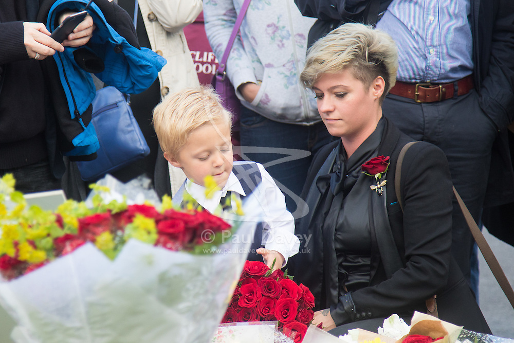 Parliament Square, Westminster, London, June 17th 2016. Following the murder of Jo Cox MP a vigil is held as friends and members of the public lay flowers, light candles and leave notes of condolence and love in Parliament Square, opposite the House of Commons. PICTURED:A Mum and her little boy lay flowers.