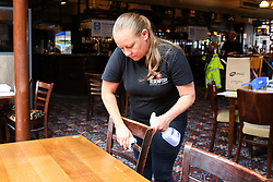 © Licensed to London News Pictures. 03/07/2020. London, UK. LINDY, the Bar Manager cleans a chair in The Toll Gate, a Wetherspoon pub in north London as the pub prepares to reopen on 4 July, the 'Super Saturday'. Pubs across the UK closed on 23 March following the coronavirus lockdown. As COVID-19 lockdown restrictions are eased, pubs will reopen on Saturday 4 July. Some pubs are planning to reopen from 6am. Photo credit: Dinendra Haria/LNP