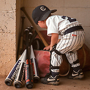 A bat boy searches for the right gear for a player during an American Legion baseball game in Columbia, S.C. ©Travis Bell Photography
