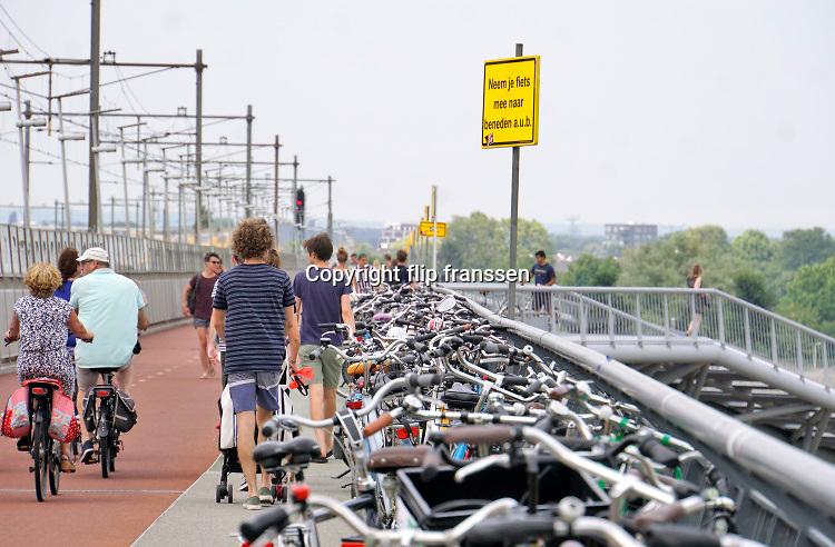 Nederland, Nijmegen, 1-8-2020 Een warme dag in de zomer . Mensen trekken naar de oevers van de waal en de spiegelwaal in het rivierpark aan de overkant van Nijmegen . De meesten komen met de fiets via de fietsbrug de snelbinder . Hier laten ze de fiets achter wat gevaarlijke situaties oplevert op het fietspad van de brug . De gemeente heeft een bord geplaatst om mensen op te roepen de fietsen mee naar beneden te nemen . De warmte, hoge temperatuur, drijft mensen naar het water . Het is verboden in de rivier te zwemmen vanwege de stroming en het drukke scheepvaartverkeer . Foto: ANP/ Hollandse Hoogte/ Flip Franssen