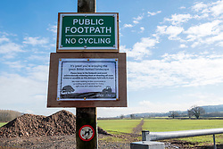 © Licensed to London News Pictures; 06/02/2021; Backwell, North Somerset, UK. A sign from The National Farmers Union asking people not to widen footpaths, go off route or walk on crops is seen along with damage and widening of a public footpath where people have been walking and running across farmland during the third UK lockdown of the Covid-19 coronavirus pandemic in England. People are allowed to go out for exercise but the numbers of people boosted by those on furlough and not at work is causing damage to green spaces and parks. Photo credit: Simon Chapman/LNP.