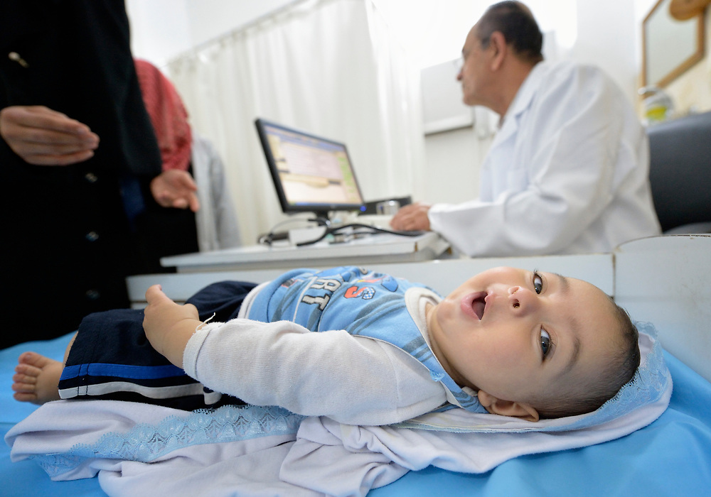 A child looks around while his mother talks with Sr. Ahmad Mathoj in a clinic in Darraj, a neighborhood of Gaza City that was hard hit by the Israeli military during the 2014 war. The clinic is run by the Department of Service for Palestinian Refugees of the Near East Council of Churches, a member of the ACT Alliance, and funded in part by the Pontifical Mission for Palestine.<br /> <br /> Health care workers say that since the 2014 war, children in Gaza are plagued with a variety of stress-related illnesses.<br /> <br /> Parental consent obtained.