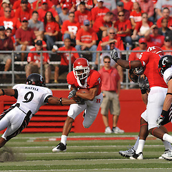 Sep 7, 2009; Piscataway, NJ, USA; Rutgers wide receiver Tim Brown (2) evades an attempted tackle by Cincinnati cornerback Dominique Battle (9) during the first half of Rutgers game against Cincinnati in NCAA college football at Rutgers Stadium.