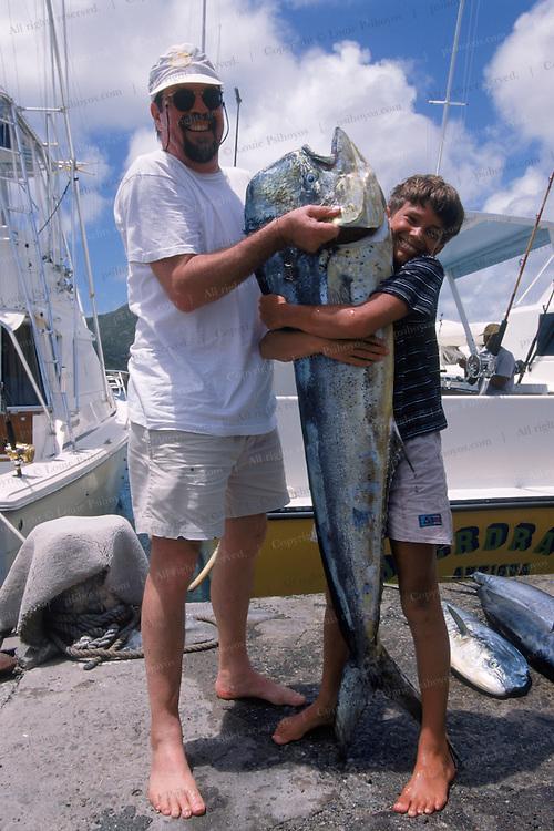 Nico Psihoyos (right) hugs a 55lb bull Mahi Mahi he caught in Antigua on a fishing boat Overdraft with friend Hans Smit (left).