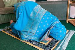 Muslim woman kneeling on the floor reciting Islamic prayers at home,