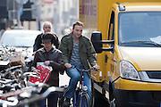 Een fietser manouvreert zich tussen een geparkeerde bestelbus en een voetganger op de Twijnstraat in Utrecht.<br /> <br /> A cyclist has to maneuver between a parked van and a pedestrian walking on the road.