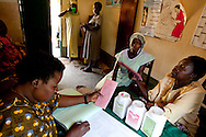 Sudan, May 2009. Nurse Betty Ajio Buku (left) fills out paperwork at the Saint Bakhita Health Centre. Tracking pregancies with detailed paperwork is important to improving the quality of health care.