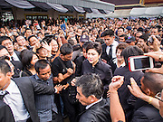 19 OCTOBER 2014 - BANG BUA THONG, NONTHABURI, THAILAND:  YINGLUCK SHINAWATRA, former Prime Minister of Thailand, walks into Apiwan Wiriyachai's cremation at Wat Bang Phai in Bang Bua Thong, a Bangkok suburb, Sunday. Apiwan was a prominent Red Shirt leader. He was member of the Pheu Thai Party of former Prime Minister Yingluck Shinawatra, and a member of the Thai parliament and served as Yingluck's Deputy Prime Minister. The military government that deposed the elected government in May, 2014, charged Apiwan with Lese Majeste for allegedly insulting the Thai Monarchy. Rather than face the charges, Apiwan fled Thailand to the Philippines. He died of a lung infection in the Philippines on Oct. 6. The military government gave his family permission to bring him back to Thailand for the funeral. His cremation was the largest Red Shirt gathering since the coup.    PHOTO BY JACK KURTZ