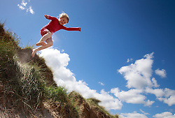 © Paul Thompson licensed to London News Pictures. 03/06/2015. Frances Tidswell-Thompson (7) jumps off sand dunes at Warkworth Beach Northumberland. Photo credit : Paul Thompson/LNP