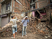 01 AUGUST 2015 - KATHMANDU, NEPAL: Workers in Kathmandu recover bricks from of a home destroyed by the earthquake. The Nepal Earthquake on April 25, 2015, (also known as the Gorkha earthquake) killed more than 9,000 people and injured more than 23,000. It had a magnitude of 7.8. The epicenter was east of the district of Lamjung, and its hypocenter was at a depth of approximately 15 km (9.3 mi). It was the worst natural disaster to strike Nepal since the 1934 Nepal–Bihar earthquake. The earthquake triggered an avalanche on Mount Everest, killing at least 19. The earthquake also set off an avalanche in the Langtang valley, where 250 people were reported missing. Hundreds of thousands of people were made homeless with entire villages flattened across many districts of the country. Centuries-old buildings were destroyed at UNESCO World Heritage sites in the Kathmandu Valley, including some at the Kathmandu Durbar Square, the Patan Durbar Squar, the Bhaktapur Durbar Square, the Changu Narayan Temple and the Swayambhunath Stupa. Geophysicists and other experts had warned for decades that Nepal was vulnerable to a deadly earthquake, particularly because of its geology, urbanization, and architecture.          PHOTO BY JACK KURTZ