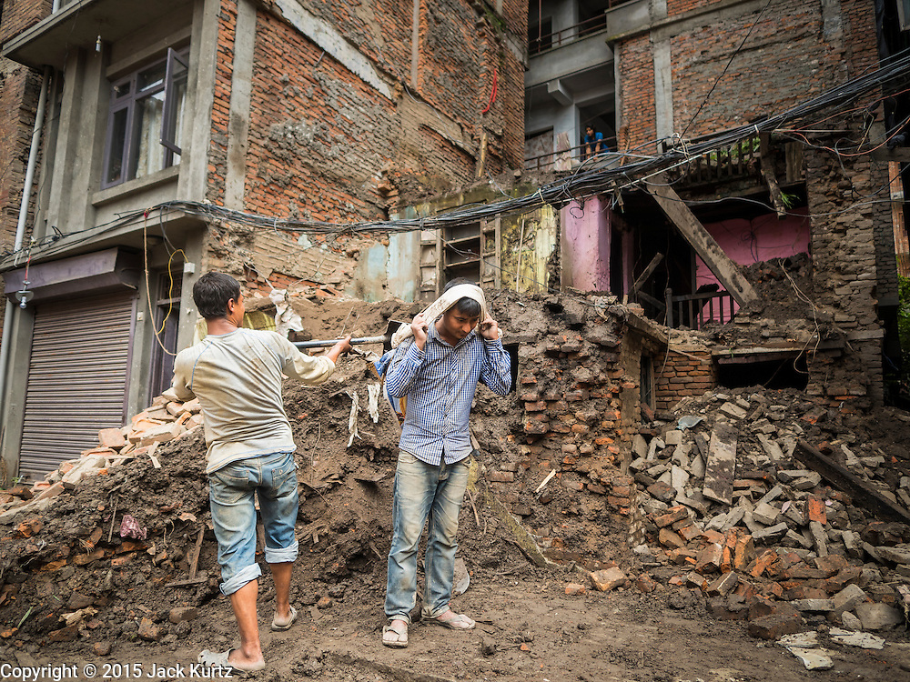 01 AUGUST 2015 - KATHMANDU, NEPAL: Workers in Kathmandu recover bricks from of a home destroyed by the earthquake. The Nepal Earthquake on April 25, 2015, (also known as the Gorkha earthquake) killed more than 9,000 people and injured more than 23,000. It had a magnitude of 7.8. The epicenter was east of the district of Lamjung, and its hypocenter was at a depth of approximately 15km (9.3mi). It was the worst natural disaster to strike Nepal since the 1934 Nepal–Bihar earthquake. The earthquake triggered an avalanche on Mount Everest, killing at least 19. The earthquake also set off an avalanche in the Langtang valley, where 250 people were reported missing. Hundreds of thousands of people were made homeless with entire villages flattened across many districts of the country. Centuries-old buildings were destroyed at UNESCO World Heritage sites in the Kathmandu Valley, including some at the Kathmandu Durbar Square, the Patan Durbar Squar, the Bhaktapur Durbar Square, the Changu Narayan Temple and the Swayambhunath Stupa. Geophysicists and other experts had warned for decades that Nepal was vulnerable to a deadly earthquake, particularly because of its geology, urbanization, and architecture.          PHOTO BY JACK KURTZ