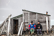 Station cook Dominik Petelski (left) and glaciologist Dariusz Ignatiuk sit together against a historic hut still standing outside the Polish Polar Station in Hornsund, Svalbard.