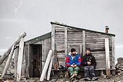 Station cook Dominik Petelski (left) and glaciologist Dariusz Ignatiuk sit together against a historic hut still standing outside the Polish Polar Station in Hornsund, Svalbard.