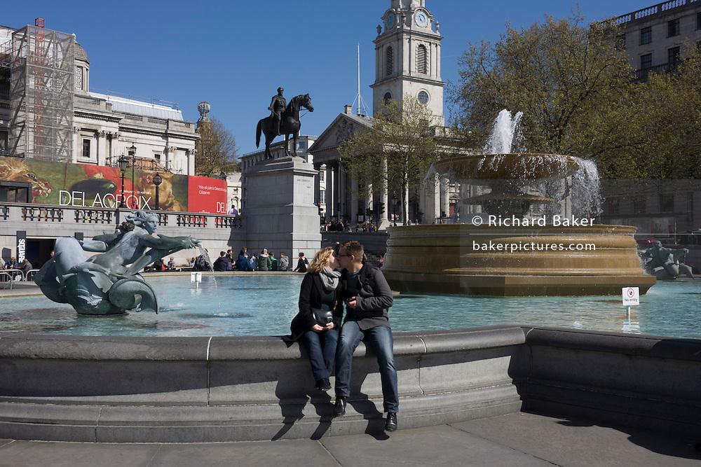 Lovers kiss near the fountains in Trafalgar Square, London.