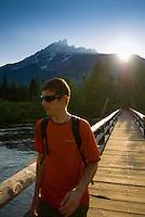 A young man hikes across a bridge at Jenny Lake in Grand Teton National Park, Wyoming.