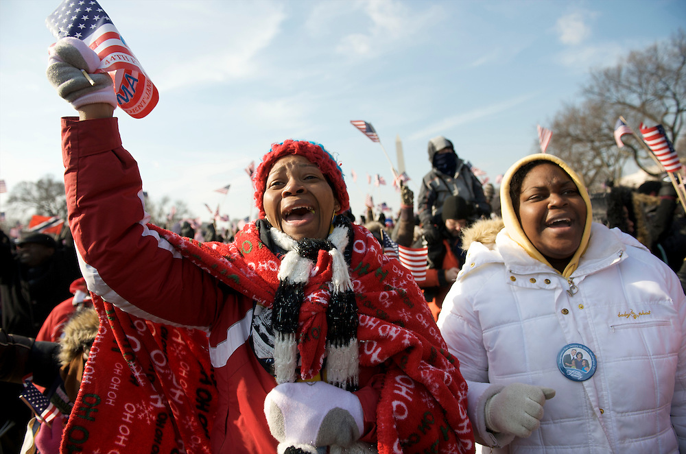 Waving flags wildly, friends celebrate during Barack Obama's Presidential Inauguration ceremony.  An estimated two million people flocked to Washington D.C. for the ceremony, enduring freezing temperatures to witness Obama take the oath of office becoming the first African-American to become President, the 44th in the history of the United States of America.¬?
