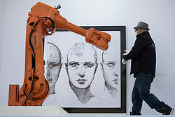 © licensed to London News Pictures. London, UK 26/09/2013. A robotic arm in Trafalgar Square, London replicates Alex Kiessling's drawing in real time as Viennese artist Alex Kiessling's (not pictured) pen movement captured by sensors and transferred via satellite to robots in both London and Berlin which replicate the drawing. Photo credit: Tolga Akmen/LNP